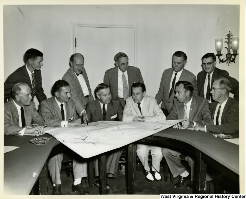 Congressman Arch A. Moore, Jr. going over a map with a group of unidentified men.