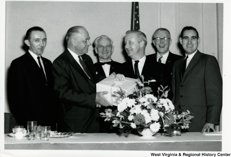 Congressman Arch A. Moore, Jr. receiving a gift from an unidentified man. Four other men are standing around them.