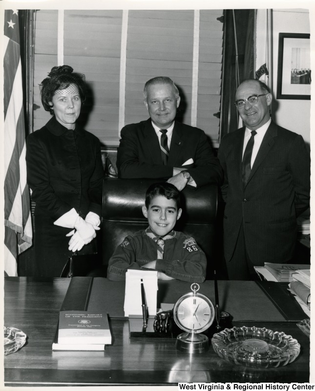 An unidentified cub scout is sitting in Congressman Arch A. Moore's office chair. Moore is standing behind the boy, while an unidentified man and woman stand on either side of Moore.