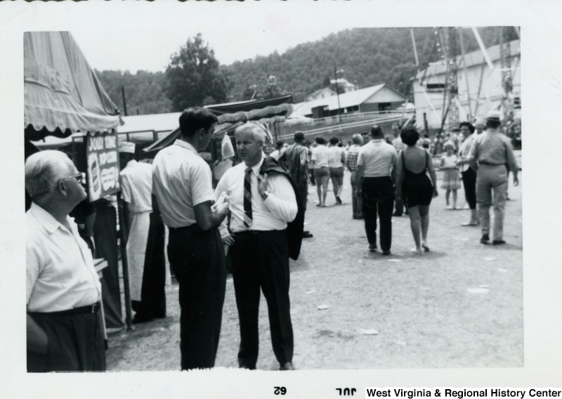 Congressman Arch A. Moore, Jr. standing with his suit jacket draped over his shoulder and talking to an unidentified man. They appear to be at a fair.