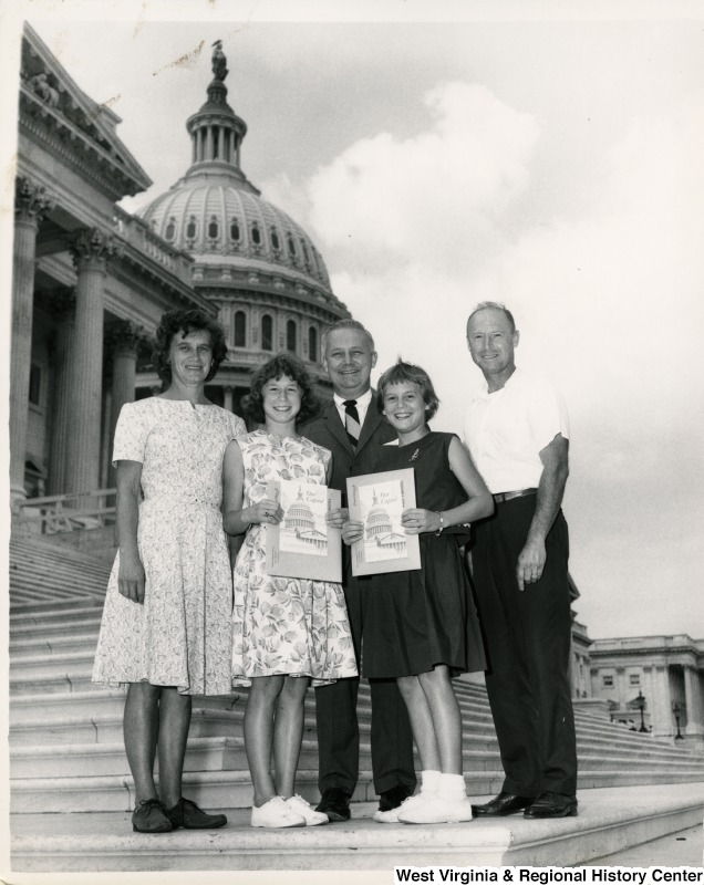 Congressman Arch A. Moore, Jr. standing on the steps of the Capitol with an unidentified family. The two girls are holding pictures of the Capitol.
