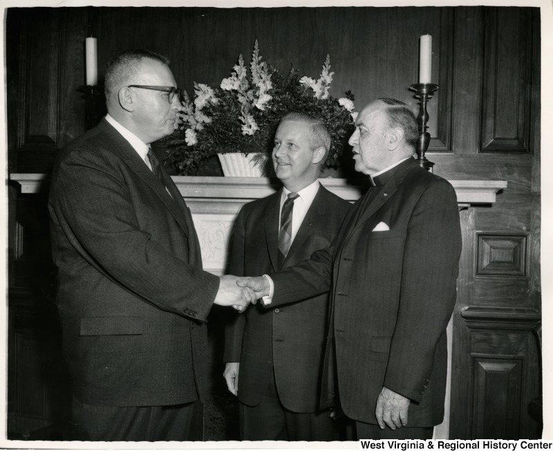 Reverend Dr. G. Ousley Brown, left, pastor of the Cove United Presbyterian Church (Weirton), shaking the hand of Reverend Dr. Bernard Braskamp, chaplain of the House of Representatives, as Congressman Arch A. Moore, Jr. looks on.
