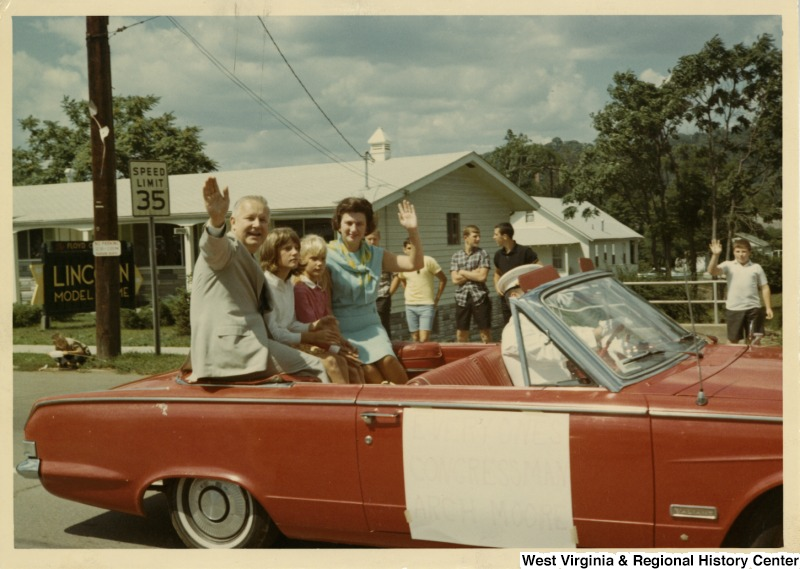Congressman Arch A. Moore, Jr., with his wife and daughters, sitting in the back of a convertible waving during a parade.