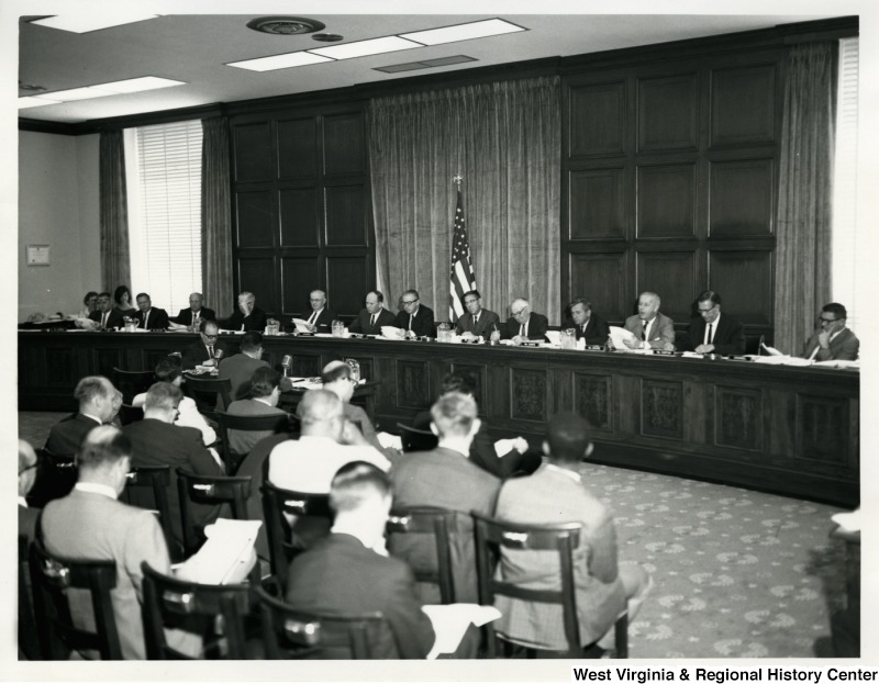 Congressman Arch A. Moore, Jr., seated third from the right, speaking during a meeting.