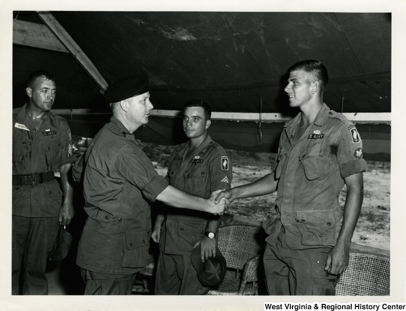 Congressman Arch A. Moore, Jr. shaking the hand of an Army Airborne officer.