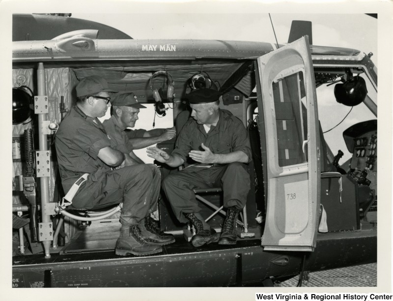 Congressman Arch A. Moore, Jr. sitting in the back of a helicopter talking to two unidentified men in uniform.