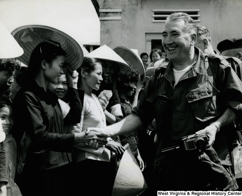 An unidentified man in uniform is shaking the hand of an unidentified Vietnamese woman in the Cau Xa Village.