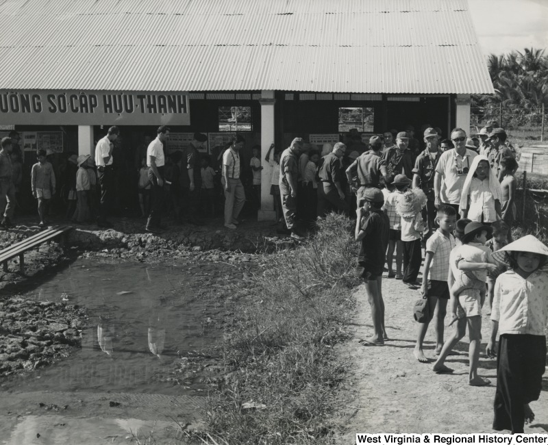 A group of people standing around a building in the Cai Be refugee camp, Vietnam.