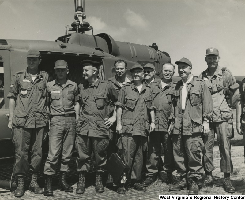 Congressman Arch A. Moore, Jr. (third from the left) standing with an unidentified group of men in front of a helicopter in Vietnam.