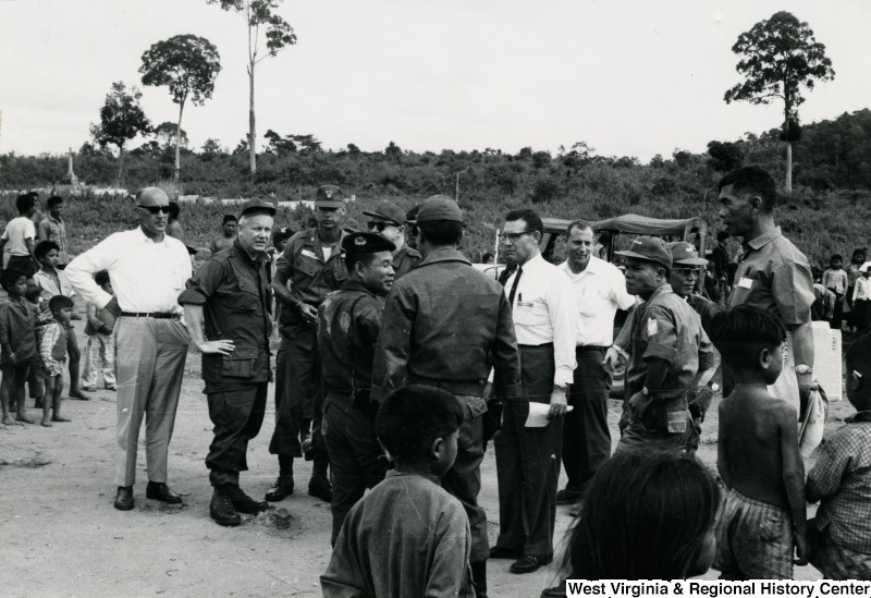 Congressman Arch A. Moore, Jr. talking to an unidentified group of men in the Kon Tum Province of Vietnam. They are surrounded by children and adults.