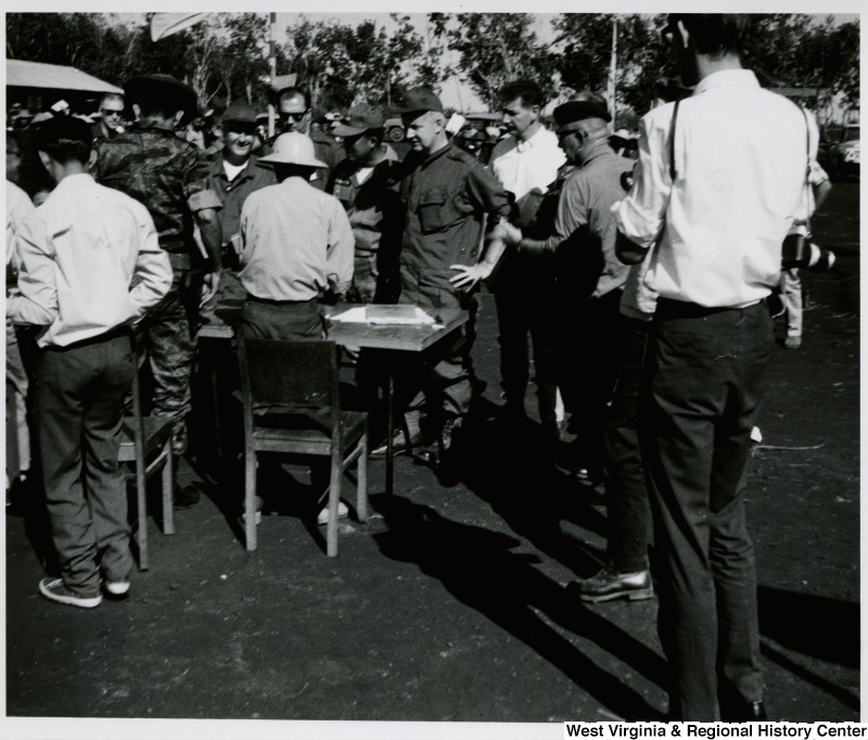 Congressman Arch A. Moore, Jr. and a group of unidentified men standing around a table in Vietnam.