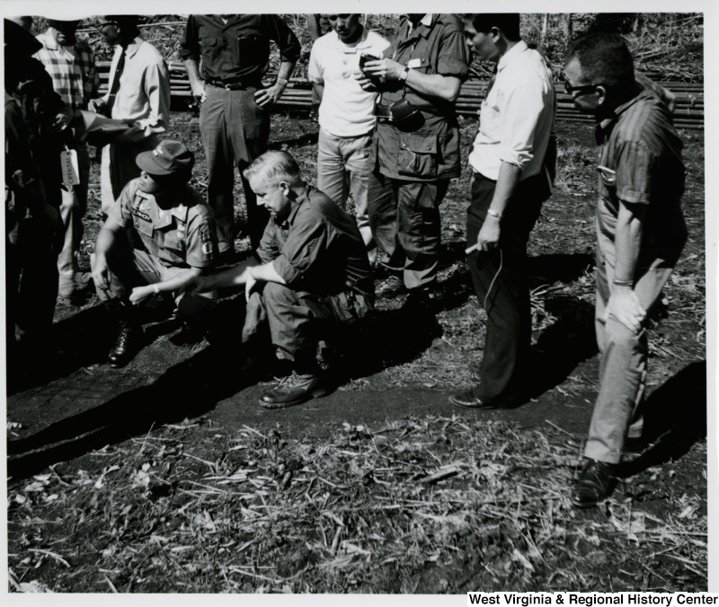 Congressman Arch A. Moore, Jr. crouching with an unidentified soldier looking at a drawing on the ground. They are surrounded by a group of unidentified men.