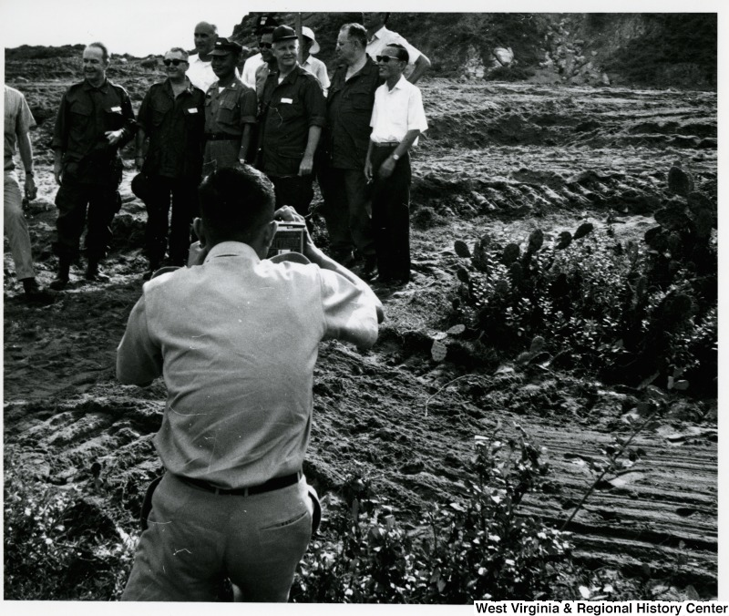 A photographer is taking a photograph of a group of men, including Congressman Arch A. Moore, Jr., in a muddy field in Vietnam.