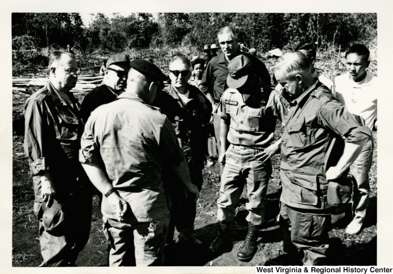 Congressman Arch A. Moore, Jr. standing with a group of soldiers in Vietnam.