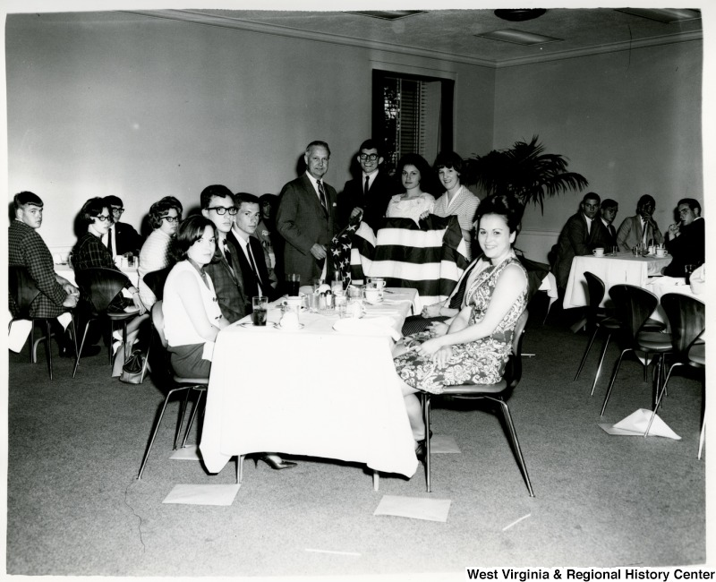 Congressman Arch A. Moore, Jr. (left) holding an American Flag with three unidentified people. There are people seated at tables around them.