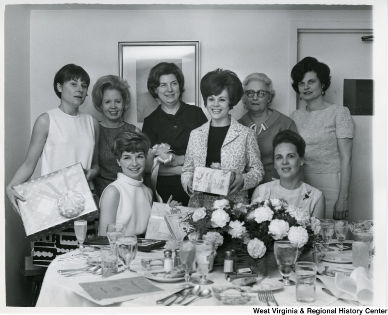 An unidentified group of women, most likely Congressman Moore's staff members, holding gifts at Suzi's shower.