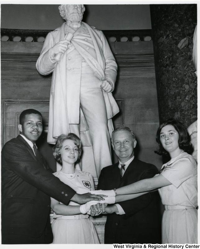 Congressman Arch A. Moore, Jr. with three 4-H members in front of a statue of Francis Harrison Pierpont. Anna A. Schmidt is standing to the left of Moore, and Linda H. Hammack is to the right. They all have their hands stacked together.