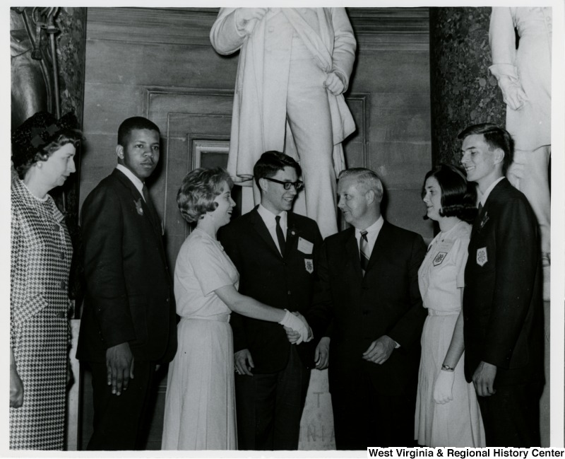 Congressman Arch A. Moore, Jr. shaking the hand of a 4-H member. Six other members of the 4-H are standing with them.  There is a statue of Francis Harrison Pierpont behind them.