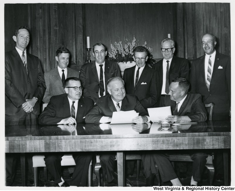 Congressman Arch A. Moore, Jr. (seated, center) meeting with eight unidentified men. They appear to be going over a document.