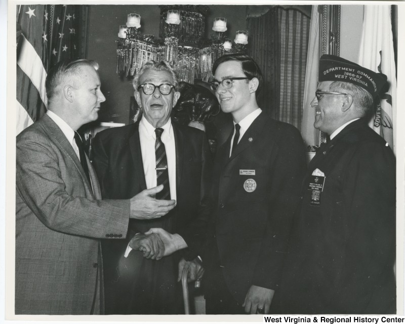 Richard A Robinson, Winner of the State Veterans of Foreign Wars annual Voice of Democracy contest, shaking the hand of Senator Everett McKinley Dirksen. Left to right: Congressman Arch A. Moore, Jr.; Senator Everett Dirksen; Richard Robinson from Fairmont, W.Va.; and State Department Commander Emmett Williams of Beckley.