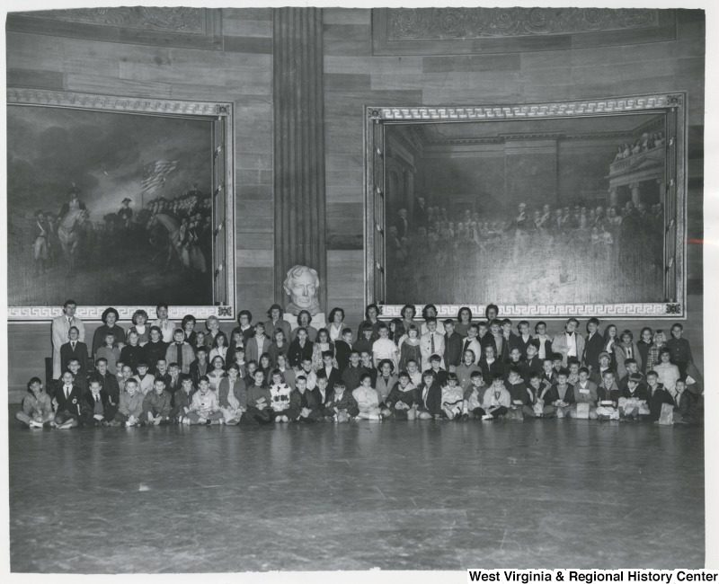 Mrs. Shelley Moore (second from the left, back row) with a unidentified class of students from the Potomac School. The are in front of two large paintings.