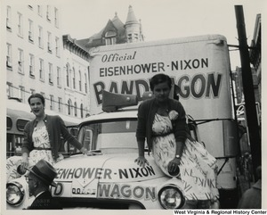 A photograph of two women posing on the hood of the Eisenhower-Nixon bandwagon truck in Wheeling, West Virginia.