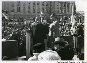 An unidentified man getting sworn into office by a judge during the inauguration of Governor Cecil H. Underwood.