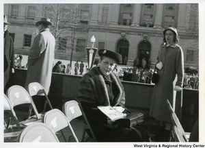 An unidentified woman sitting with the inauguration party and First Lady Hovah Hall Underwood standing in the background on the right. Two unidentified men are standing in the background talking on the left.