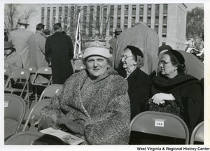 An unidentified woman sitting in chair 127 during Governor Underwood's inauguration. Behind her are two unidentified women sitting and some unidentified men are standing.
