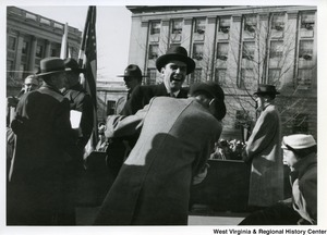 Governor Cecil H. Underwood laughing at is inauguration as a unidentified man hugs him while a group of unidentified men are standing in the background.