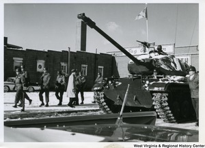 A tank with soldiers walking beside it during the parade for Governor Cecil H. Underwood's inauguration.