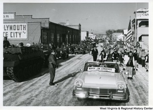 Governor Cecil Underwood's inauguration parade, featuring military vehicles, officers, Mayor J.W. Londeree's vehicle, and a band.