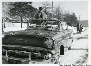 Mrs. John A. Jones, associate chairman, standing in the back of a Chevrolet car for the inauguration parade of Governor Cecil H. Underwood.