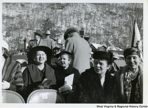A photograph of four unidentified women sitting during Governor Cecil H. Underwood's inauguration. In the background four unidentified men are standing.