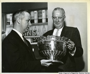 "Congressman Arch A. Moore, Jr. presenting a silver punch bowl to John C. McConnell, President of the Ohio Valley Board of Trade. The silver punch bowl was given by the citizens of Wheeling to the officer's mess on the U.S. gunboat ""Wheeling"" in September 1897."