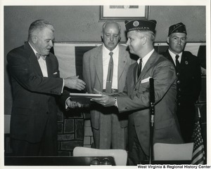 A photograph of an unidentified veteran at the Veterans Service Office in Weirton, W.Va, presenting Congressman Moore with a plaque.