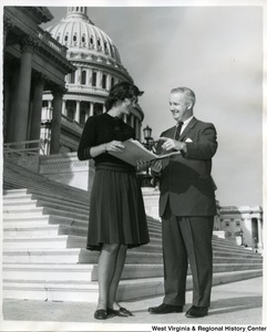 Congressman Arch Moore, Jr. with an unidentified woman holding a book in front of the Capitol Building.