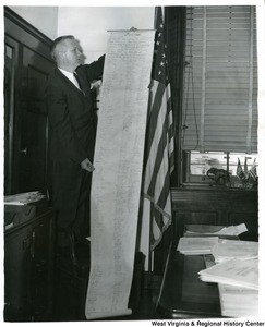 Congressman Arch Moore, Jr standing on a chair and holding out a petition from the teachers and students of Weir High School, Weirton, W.Va.. The petition is for the continuance of religious prayer during the opening exercises of each school day and the pledge of allegiance to the flag.