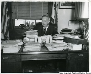 Congressman Arch Moore, Jr sitting behind his desk, which is piled high with paperwork.
