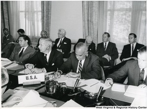 A photograph of Congressman Arch Moore, Jr., looking to the left, with other unidentified U.S. representatives during a meeting.