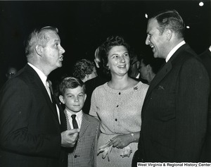 Congressman Arch Moore, Jr. talking to an unidentified individual. His wife, Shelley Moore, and son, Arch A. Moore III, are standing beside him.