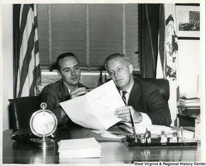 Congressman Arch Moore, Jr. with Noel Foreman, an intern in Moore's Washington Office. Moore and Foreman are discussing bill H.R. 7457. Noel was one of three young West Virginians who interned in the Congressman's office.