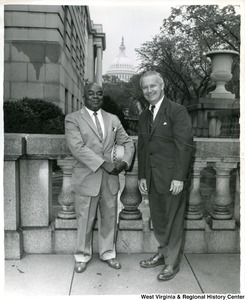 Congressman Arch Moore, Jr. standing with an unidentified man. The Capitol Building is in the background.