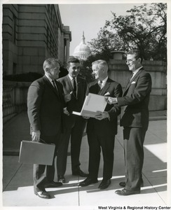 Congressman Arch Moore, Jr. with three unidentified men looking at the Comprehensive Plan for Paden City, West Virginia. The Capitol Building is in the background.