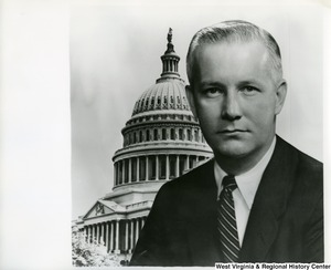 A portrait of Congressman Arch Moore, Jr. posed in front of a backdrop of the Capitol Building.