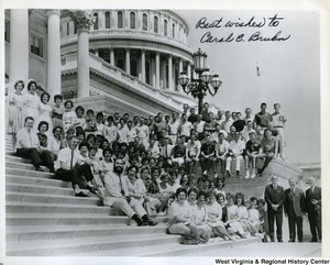 "Congressman Arch Moore, Jr. with a large unidentified group of people siting on the Capitol building steps. The photo is signed ""Best wishes to Carol E. Bruln?"""