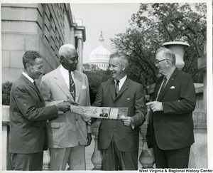 Congressman Arch Moore, Jr. (second from right) showing The Capitol Guide brochure to Roy Barnes, J.H. Davis, and Wade Augerbright. The Capitol Building is in the background.