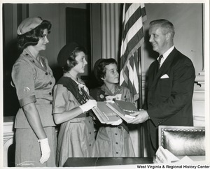Congressman Arch Moore, Jr with Girl Scout Troop Leader Mrs. Kay Morris and Girl Scouts Deborah Ziska and Carolyn Snow of Troop 2141. They are presenting Moore with four Girl Scout Handbooks.