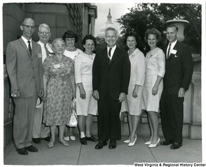 Congressman Arch Moore, Jr. and Shelley Moore with a group of unidentified individuals. The Capitol Building is in the background.