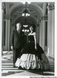 Congressman Arch Moore, Jr. with a woman identified as either Genevive de Beaucorps or Aline Petershchmitt, who is wearing a ball gown.